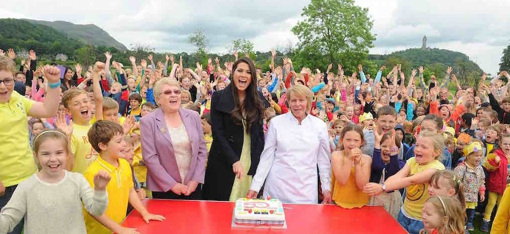 Bridge Ofd Allan Primary 50th Anniversary celebrations  Current Mis Scotland Mhairi Fergusson cuts the cake with Dinner Lady Lorna McFarlane and Jean Bremner,cake maker and who also has had 4 generations pass through the school Photography by Whyler Photos of Stirling - www.whylerphotos.com